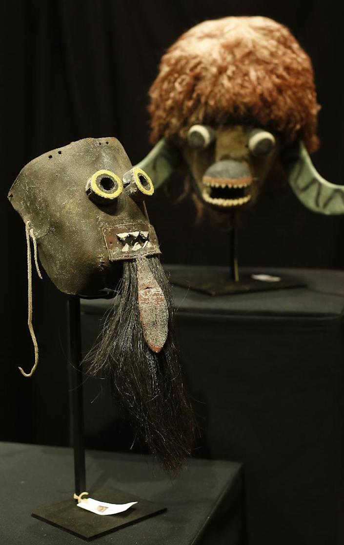 A Puebloan Chakwaina mask (L, circa 1900/1910) and a Kachina Buffalo mask (circa 1910/1920) are on display among other artefacts made by Native American tribes before their sale at the Drouot auction house in Paris on December 14, 2014 (AFP Photo/Thomas Samson)