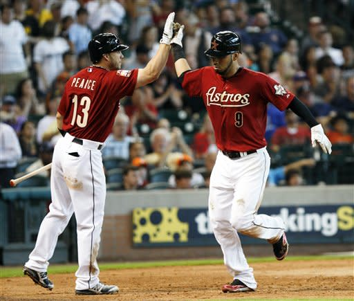 Houston Astros' Marwin Gonzalez (9) is congratulated by Steve Pearce (13) as he runs home to score against the Pittsburgh Pirates in the sixth inning of a baseball game, Sunday, July 29, 2012 in Houston. The Astros won 9-5. (AP Photo/Eric Kayne)