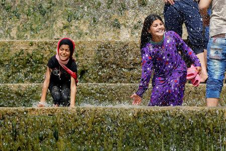 "Iraqi girls play with water as they enjoy their Friday holiday with their family at Shallalat district (Arabic for ""waterfalls"") in eastern Mosul"