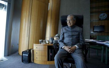 Malaysia's former prime minister Mahathir Mohamad poses for a photograph following an interview with Reuters at his desk in Petronas Towers, Kuala Lumpur, Malaysia