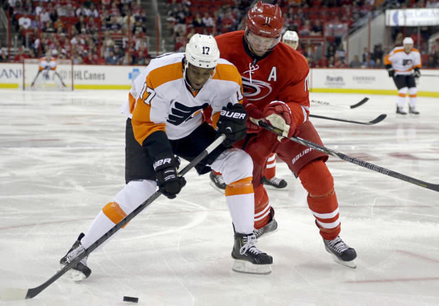 Philadelphia Flyers' Wayne Simmonds (17) and Carolina Hurricanes' Jordan Staal (11) chase the puck during the first period of an NHL hockey game in Raleigh, N.C., Sunday, Oct. 6, 2013. (AP Photo/Gerry Broome)