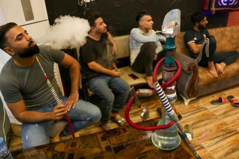 Iraqi men smoke waterpipes at a coffee shop in Iraq's holy city of Karbala, where the pipes are traditionally made of locally carved wood