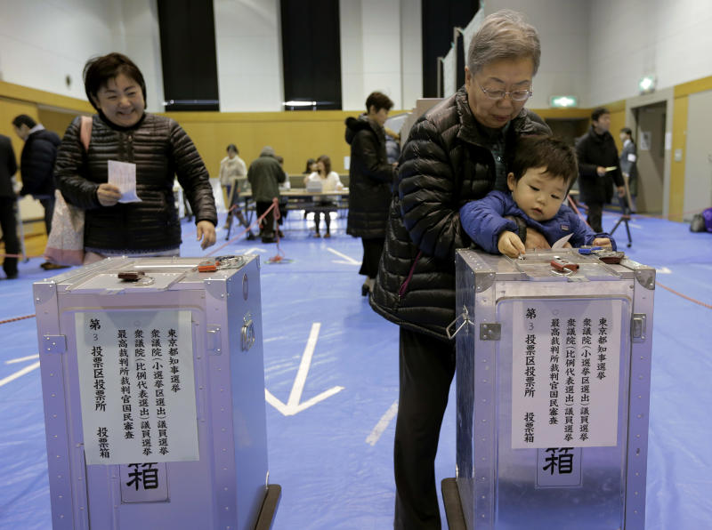 A boy places his grandmother's vote into a ballot box at a polling station in Tokyo, Sunday, Dec. 16, 2012. Voters cast their ballots Sunday in parliamentary elections which are likely to hand power back to a conservative party that ruled Japan for most of the post-war era.  (AP Photo/Itsuo Inouye)