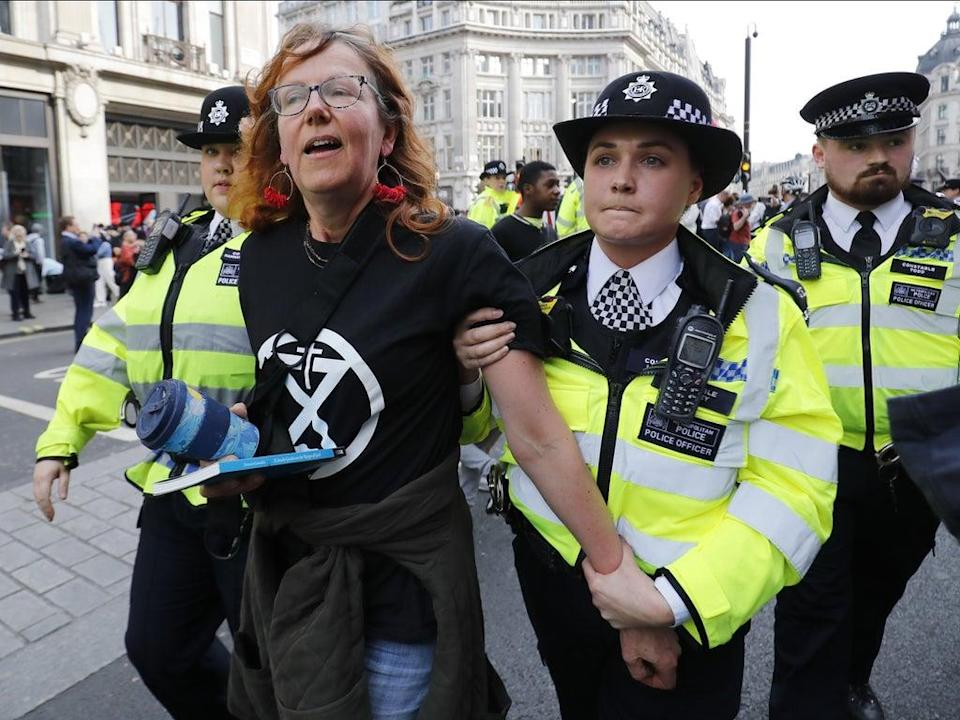Police officers escorting a climate activist during protests in April 2019 (AFP/Getty)