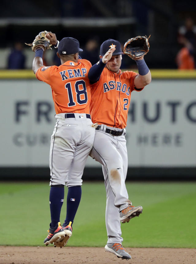 Houston Astros' Tony Kemp (18) and Alex Bregman (2) share congratulations after the Astros defeated the Seattle Mariners 8-7 in 14 innings in a baseball game Thursday, June 6, 2019, in Seattle. (AP Photo/Elaine Thompson)