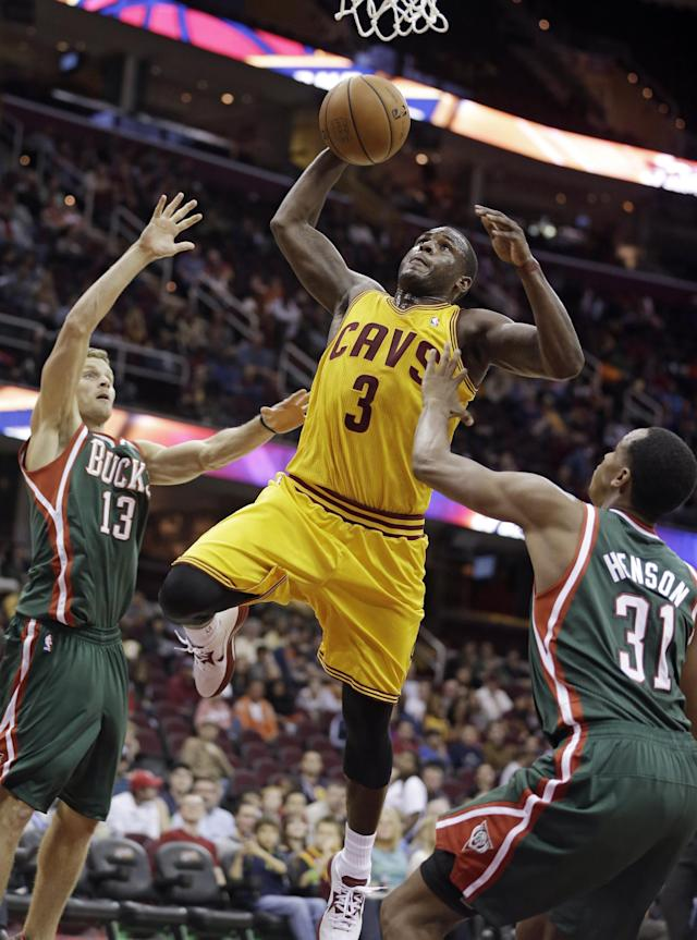 Cleveland Cavaliers' Dion Waiters (3) jumps to the basket against Milwaukee Bucks' Luke Ridnour (13) and John Henson during the first half of an NBA preseason basketball game Tuesday, Oct. 8, 2013, in Cleveland. (AP Photo/Tony Dejak)