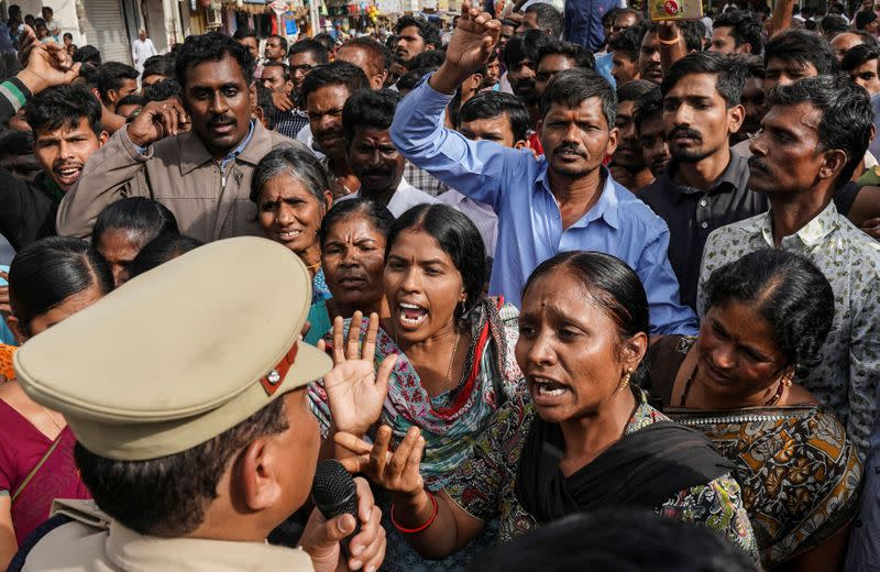 Demonstrators argue with a police officer during a protest against the alleged rape and murder of a 27-year-old woman in Shadnagar