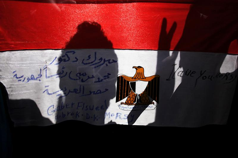 """A man's shadow is reflected on Egypt's national's flag with Arabic writing that reads, """"congratulations Dr. Mohammed Morsi president of Egypt,"""" in Tahrir square, Cairo, Egypt, Sunday, June 24, 2012. Mohammed Morsi was declared Egypt's first Islamist president on Sunday after the freest elections in the country's history, narrowly defeating Hosni Mubarak's last Prime Minister Ahmed Shafiq in a race that raised political tensions in Egypt to a fever pitch. (AP Photo/Manu Brabo)"""