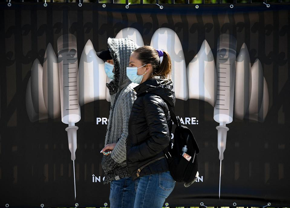 People wearing protection masks walk by a banner showing syringes as vampire fangs during the vaccination marathon organized at the