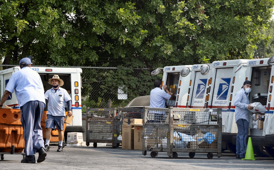 Postal workers load their mail delivery vehicles at the Panorama city post office on Thursday, Aug. 20, 2020 in the Panorama City section of Los Angeles. (AP Photo/Richard Vogel)