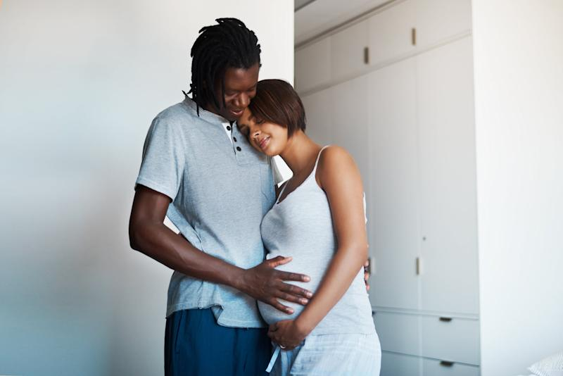 Shot of happy young man posing with his pregnant wife at home