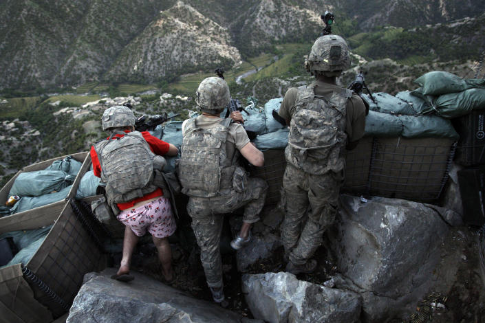 Soldiers from the U.S. Army First Battalion, 26th Infantry take defensive positions at firebase Restrepo after receiving fire from Taliban positions in the Korengal Valley of Afghanistan's Kunar Province on May 11, 2009. Spc. Zachary Boyd of Fort Worth, TX, far left was wearing 'I love NY' boxer shorts after rushing from his sleeping quarters to join his fellow platoon members. From far right is Spc. Cecil Montgomery of Many, LA and Jordan Custer of Spokan, WA, center. (AP Photo/David Guttenfelder, File)