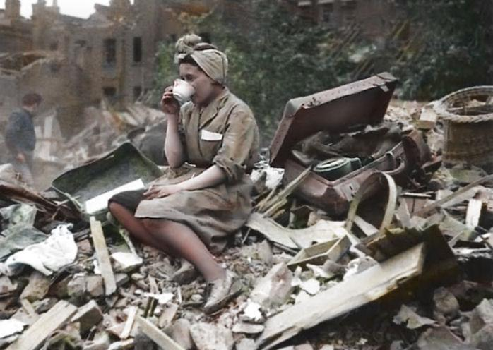 <p>A woman sits on a pile of rubble and enjoys a cup of tea in a quintessentially British act of defiance.<br /> (Royston Leonard/mediadrumworld.com) </p>