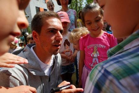 Philipp Lahm, former Germany captain and the country's UEFA EURO 2024 bid ambassador, talks to children as he signs autographs during his visit to the German language school in Moscow, Russia June 18, 2018. REUTERS/Sergei Karpukhin