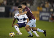 Colorado Rapids midfielder Braian Galvan, front, pursues the bal with Vancouver Whitecaps midfielder Michael Baldisimo in the second half of an MLS soccer match Sunday, Sept. 19, 2021, in Commerce City, Colo. The game ended in a 1-1 tie. (AP Photo/David Zalubowski)