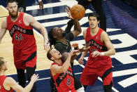 Minnesota Timberwolves' Naz Reid, center, battles for the rebound with Toronto Raptors' Malachi Flynn (8) in the first half of an NBA basketball game, Friday, Feb. 19, 2021, in Minneapolis. (AP Photo/Jim Mone)