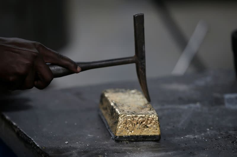 An employee uses a hammer to clean a gold ingot during the refining process at AGR (African Gold Refinery) in Entebbe