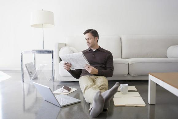 A man reading a newspaper while seated against a beige couch on his living room floor with an open laptop.