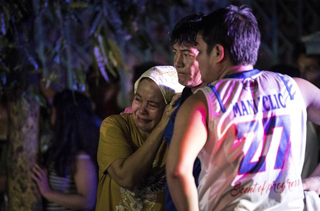 Relatives of Aldrin Castillo, an alleged drug user killed by unidentified assailants, grieve as they arrive at the crime scene in Manila on Oct. 3, 2017. (Noel Celis/AFP/Getty Images)