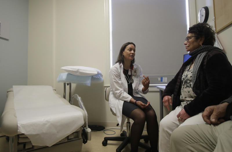 In this April 9, 2019 photo, Dr. Megan Mahoney, left, talks with patient Consuelo Castaneda at the Stanford Family Medicine office in Stanford, Calif. Health care experts say the changing, fragmented nature of care is precisely why people still need someone who looks out for their overall health, which is the traditional role of primary care physicians like family doctors and pediatricians. (AP Photo/Jeff Chiu)