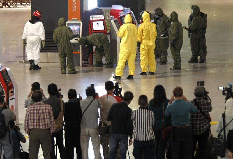 Hazmat crews investigate the check in kiosk machines at Kuala Lumpur International Airport 2 in Sepang, Malaysia on Sunday, Feb. 26, 2017. Malaysian police ordered a sweep of Kuala Lumpur airport for toxic chemicals and other hazardous substances following the killing of Kim Jong Nam. (AP Photo/Daniel Chan)