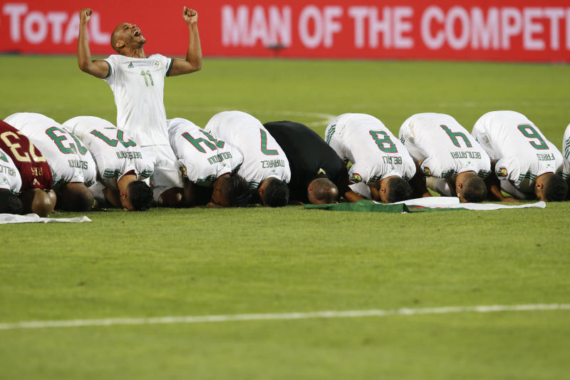 Algerian players pray after the African Cup of Nations final soccer match between Algeria and Senegal in Cairo International stadium in Cairo, Egypt, Friday, July 19, 2019. (AP Photo/Ariel Schalit)