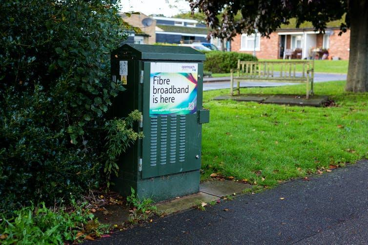 A green internet cabinet on a grassy verge next to a pavement.