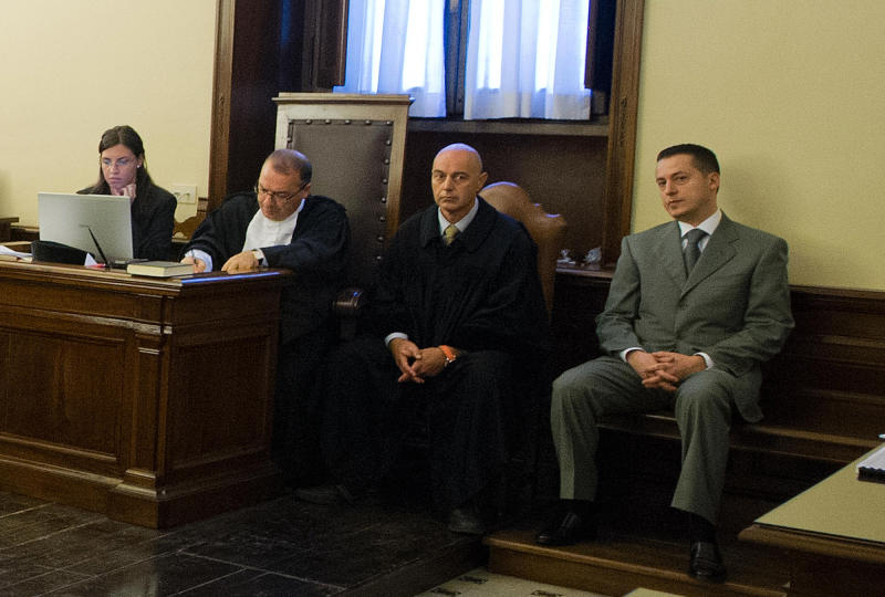 """RETRANSMISSION TO PROVIDE ALTERNATIVE CROP - In this photo released by the Vatican paper L'Osservatore Romano, pope's butler Paolo Gabriele, right, sits in the wood-trimmed courtroom of the Vatican tribunal, at the Vatican, Saturday, Sept. 29, 2012. The Vatican opened the public trial Saturday of the pope's butler for allegedly stealing and leaking papal correspondence to a journalist, the most embarrassing scandal of Pope Benedict XVI's papacy. Paolo Gabriele, a 46-year-old father of three, faces up to four years in prison if he is convicted of aggravated theft in the worst security breach in the Vatican's recent history. He has already confessed, saying he acted to shed light on what he called """"evil and corruption"""" in the church, and asked to be pardoned by the pope, something Vatican watchers say is a given if he is convicted. (AP Photo/L'Osservatore Romano)"""