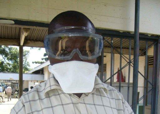 A Ugandan health official wears protective gear as he deals with an ebola outbreak at the Bityo hospital in 2007. Uganda's president has warned against shaking hands and other physical contact after the first reported death from the deadly Ebola virus in the capital Kampala