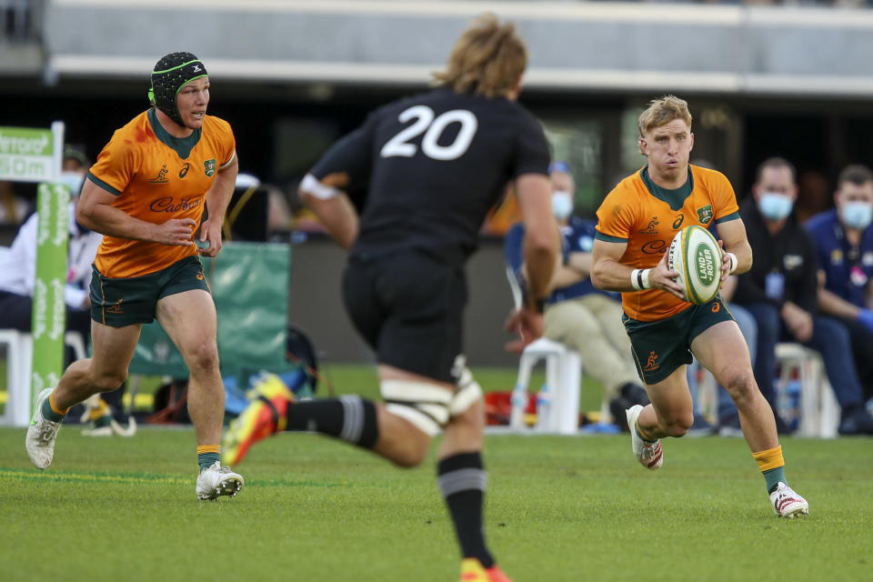 Australia's Tate McDermott, right, makes a run as teammate Australia's Michael Hooper, left, watches during the Rugby Championship game between the All Blacks and the Wallabies in Perth, Australia, Sunday, Sept. 5, 2021. (AP Photo/Gary Day)