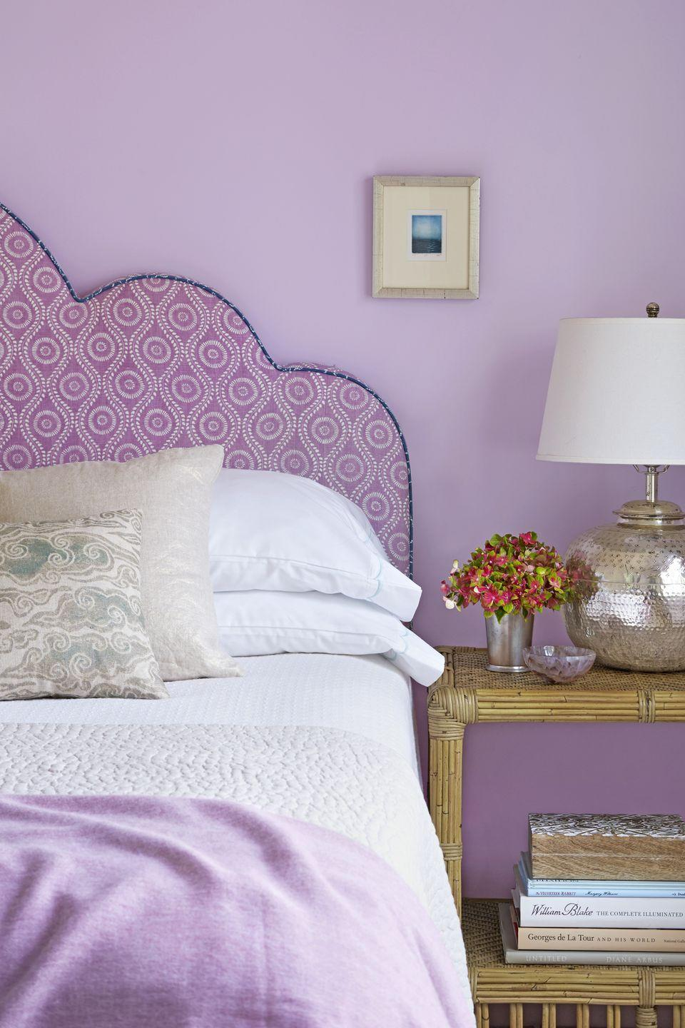 """<p>In this well-appointed feminine bedroom, <a href=""""http://caitlinmoraninteriors.com/"""" rel=""""nofollow noopener"""" target=""""_blank"""" data-ylk=""""slk:designer Caitlin Moran"""" class=""""link rapid-noclick-resp"""">designer Caitlin Moran </a>mastered the art of tone on tone with pale lilac walls, a purple upholstered headboard, and a lilac throw. White bedding breaks up the similar shades and keeps it from feeling overwhelming. </p><p><strong>Get the Look: </strong><br>Wall Paint Color: <a href=""""https://www.benjaminmoore.com/en-us/color-overview/find-your-color/color/2071-70/misty-lilac"""" rel=""""nofollow noopener"""" target=""""_blank"""" data-ylk=""""slk:Misty Lilac by Benjamin Moore"""" class=""""link rapid-noclick-resp"""">Misty Lilac by Benjamin Moore</a></p>"""