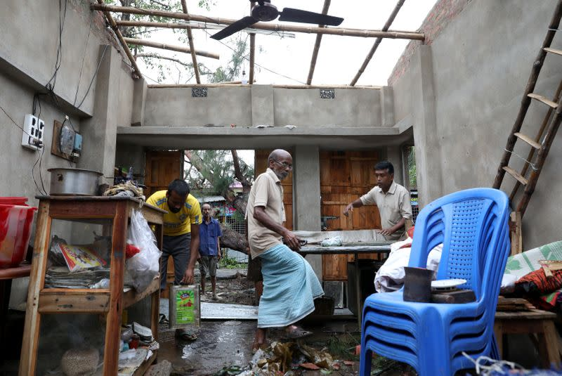 Men salvage items from a damaged shop after Cyclone Amphan made its landfall, in South 24 Parganas district