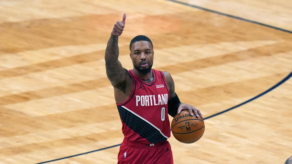Damian Lillard gives a thumbs up as he dribbles with the other hand during a game.