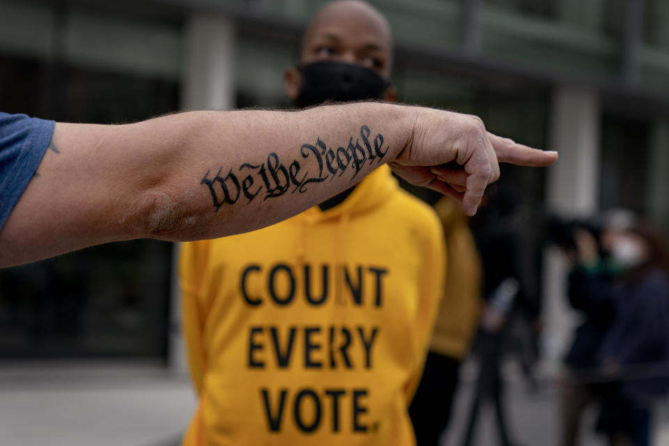 """In this Nov. 5, 2020, file photo, the tattoo """"We The People"""", a phrase from the United States Constitution, decorates the arm of Trump supporter Bob Lewis, left, as he argues with counter protestor Ralph Gaines while Trump supporters demonstrate against the election results outside the central counting board at the TCF Center in Detroit. President Donald Trump and his allies have fomented the idea of a """"rigged election"""" for months, promoting falsehoods through various media and even lawsuits about fraudulent votes and dead voters casting ballots. While the details of these spurious allegations may fade over time, the scar it leaves on American democracy could take years to heal. (AP Photo/David Goldman, File)"""