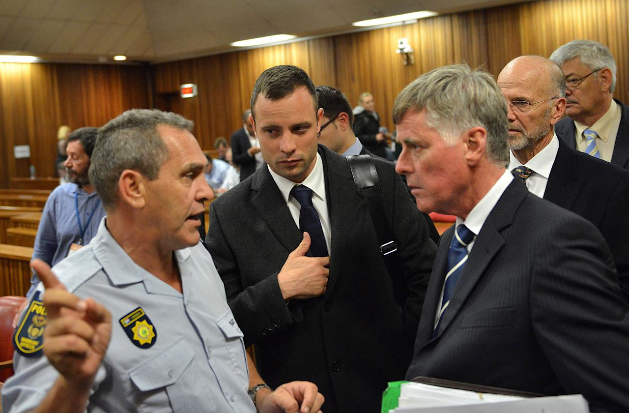 Oscar Pistorius, center, during a break inside court on the second day of his trial at the high court in Pretoria, South Africa, Tuesday, March 4, 2014. Pistorius is charged with murder for the shooting death of his girlfriend, Reeva Steenkamp, on Valentines Day in 2013. (AP Photo/Antoine de Ras, Pool)