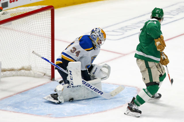 St. Louis Blues goaltender Jake Allen, left, makes a pad save on the shot by Dallas Stars center Andrew Cogliano, right, during the third period of an NHL hockey game in Dallas, Friday, Feb. 21, 2020. The Blues won 5-1. (AP Photo/Ray Carlin)