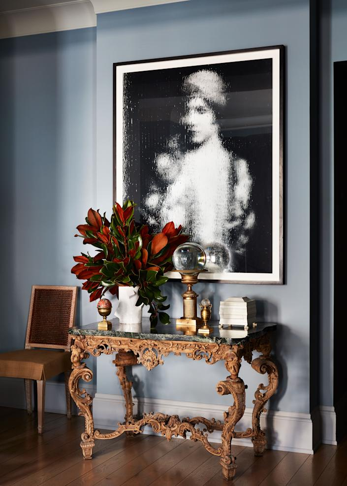 """I love the tension of modern with traditional, the play of periods, the contradictions,"" says Nunnerley, referring to a contemporary photo by Gregor Hildebrandt in the entrance hall hanging above a Louis XIV console she bought at auction. ""Someone had gilded the console to death but I could see how special the carving was, so I stripped it."""