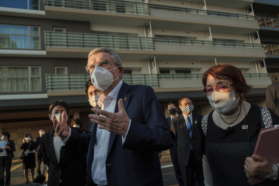 "IOC President Thomas Bach wearing a protective mask gestures while speaking to journalists during a visit to Olympic and Paralympic Village in Tokyo Tuesday, Nov. 17, 2020. Bach said during this week's trip to Tokyo that he is ""encouraging"" all Olympic ""participants"" and fans to be vaccinated - if one becomes available - if they are going to attend next year's Tokyo Olympics. (Nicolas Datiche/Pool Photo via AP)"