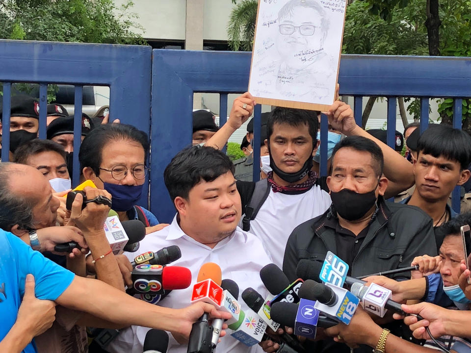 "Protest leader Parit ""Penguin"" Chiwarak, center, speaks to journalists outside the criminal court after he was released on bail Saturday, Aug. 15, 2020 in Bangkok, Thailand. Parit was arrested by police Friday on a sedition charge in connection with a July 18 protest. (AP Photo/Busaba Sivasomboon)"