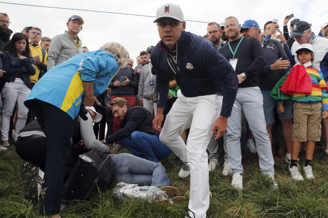 FILE - In this Friday, Sept. 28, 2018 file photo Brooks Koepka of the US offers a golf glove to a spectator he injured when his ball hit her on the 6th hole during his fourball match on the opening day of the 42nd Ryder Cup at Le Golf National in Saint-Quentin-en-Yvelines, outside Paris, France. Ryder Cup organizers say they are alarmed by the news that a spectator hit by a Brooks Koepka's tee shot at the Ryder Cup says she has lost sight in her right eye. (AP Photo/Francois Mori, File