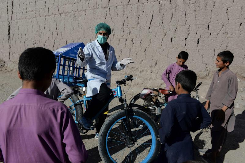 Image: 27-year-old Afghan cyclist Idrees Syawash talks to residents during his awareness campaign against the COVID-19 coronavirus in the Surkh Rod district of Nangarhar province (Noorullah Shirzada / AFP - Getty Images)
