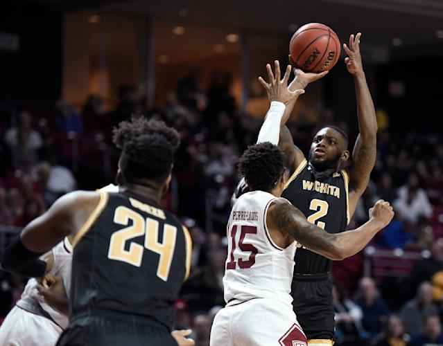 Wichita State's Jamarius Burton (2) shoots over Temple's Nate Pierre-Louis (15) during the first half of an NCAA college basketball game Wednesday, Jan. 15, 2020, in Philadelphia. (AP Photo/Michael Perez)