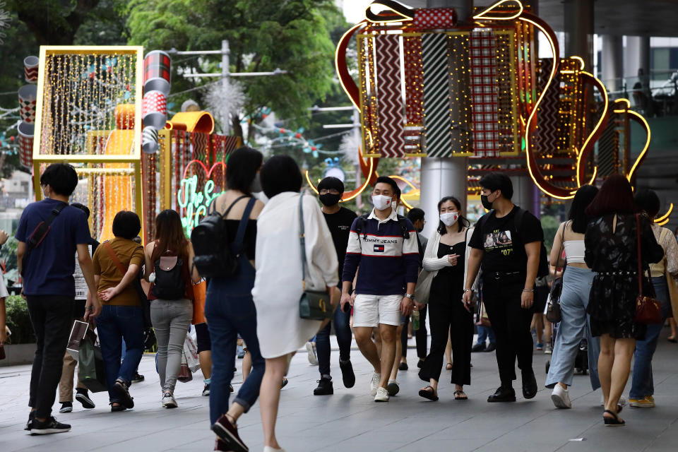 SINGAPORE - DECEMBER 24: People wearing protective mask walk past Christmas decorations along the Orchard Road shopping belt on December 24, 2020 in Singapore. As Singapore prepares to further ease COVID-19 restrictions from December 28, the government reported its first COVID-19 case carrying the potentially more contagious strain of the virus circulating in the United Kingdom yesterday. As of 24 December, the Ministry of Health confirmed 13 new imported COVID-19 cases in the wider community bringing the country's total to 58,495. (Photo by Suhaimi Abdullah/Getty Images)