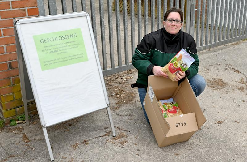 Verena Kaspari holds open a box of supplies next to a sign in German, indicating that the zoo is closed and they are in financial trouble