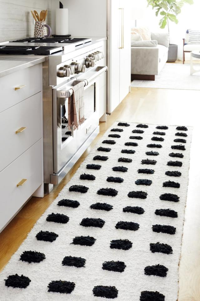 """<p>If you're looking for a low-tech way to warm up the floors in your home, try a trick interior designers use often and lay down area rugs. In the kitchen of the <a href=""""https://www.realsimple.com/home-organizing/decorating/decorating-tips-techniques/real-simple-home-2019"""" target=""""_blank"""">2019 Real Simple Home</a>, designer Cortney Bishop placed a textured runner between the sink and the fridge, creating a soft spot to do dishes or meal prep. Look for rugs made of thick, warm materials, like wool, and opt for those with textures and patterns so they look as warm as they feel. </p> <p><strong>To buy: </strong>Providencia Runner Rug, <a href=""""https://pampa.com.au/products/providencia-runner"""" target=""""_blank"""">pampa.com</a>. </p>"""