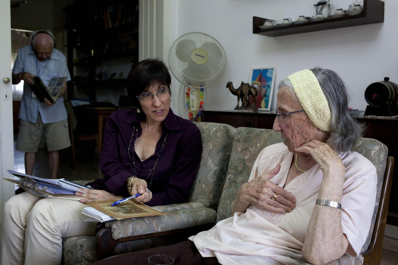 In this photo take on Sunday, May 5, 2013, Holocaust survivor Rivka Fringeru, 82, right, hold her chest as she speaks to Cynthia Wroclawski, director of Yad Vashem names collection project as they sit at her living room in Rehovot, central Israel. With a hand on her chest and moistness building in her eyes, 82-year-old Rivka Fringeru battled back tears as she reeled off a list of names she has rarely voiced in the past 70 years. First her father, Moshe, then her mother, Hava, and finally her two older brothers, Michael and Yisrael - all perished in the Holocaust after the Harabju family from Dorohoi, Romania was rounded up in 1944 and sent to ghettos and camps. Only Rivka and her brother Marco survived, and like so many others they spent the rest of their lives trying to move on and forget. Now, Yad Vashem, Israel's national Holocaust memorial and museum, is asking them to remember. (AP Photo/Ariel Schalit)
