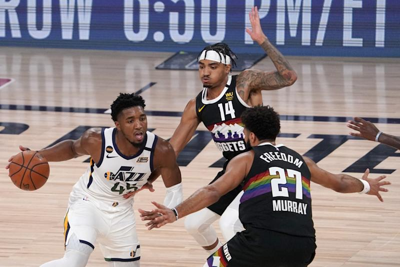 Utah's Donovan Mitchell looks for an opening between Denver's Gary Harris and Jamal Murray.
