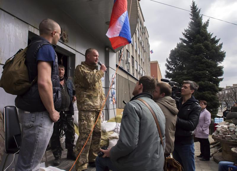 A pro-Russian activist, calling himself Vasily, second left, speaks to other protesters at barricades, with a Russian national flag in front of an entrance to the Ukrainian regional office of the Security Service in Luhansk, 30 kilometers (20 miles) west of the Russian border, in Ukraine, Wednesday, April 9, 2014. Ukrainian Interior Minister Arsen Avakov said the standoff in Luhansk and the two neighboring Russian-leaning regions of Donetsk and Kharkiv must be resolved within the next two days either through negotiations or through the use of force, the Interfax news agency reported. (AP Photo/Igor Golovniov)