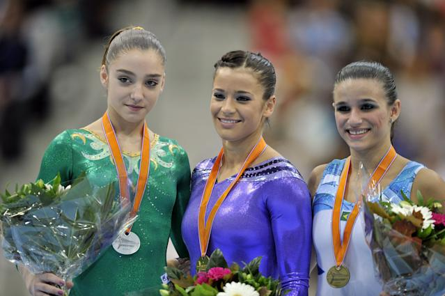Gold medallist US Alicia Sacramone (C) , silver medallist Russia's Aliya Mustafina (L) and bronze medallist Brazil's Jade Fernandes Barbosa (R) pose on the podium at the end of the women's vault final at the 42nd Artistic Gymnastics World Championships, on October 23, 2010, in Rotterdam. AFP PHOTO / BORIS HORVAT (Photo credit should read BORIS HORVAT/AFP/Getty Images)