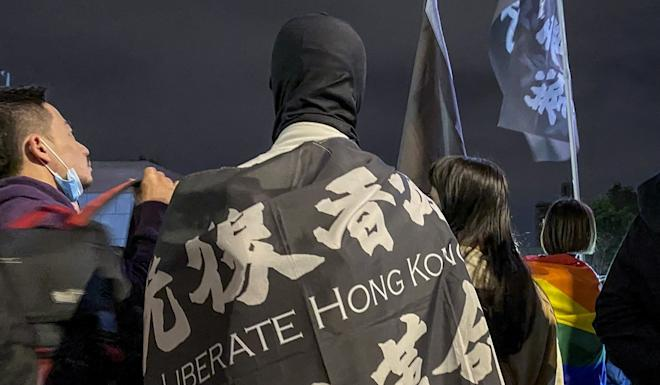 A Hong Kong protester at the Taiwan rally is draped in a flag bearing the movement's rallying cry of 'Liberate Hong Kong; revolution of our times'. Photo: Kimmy Chung